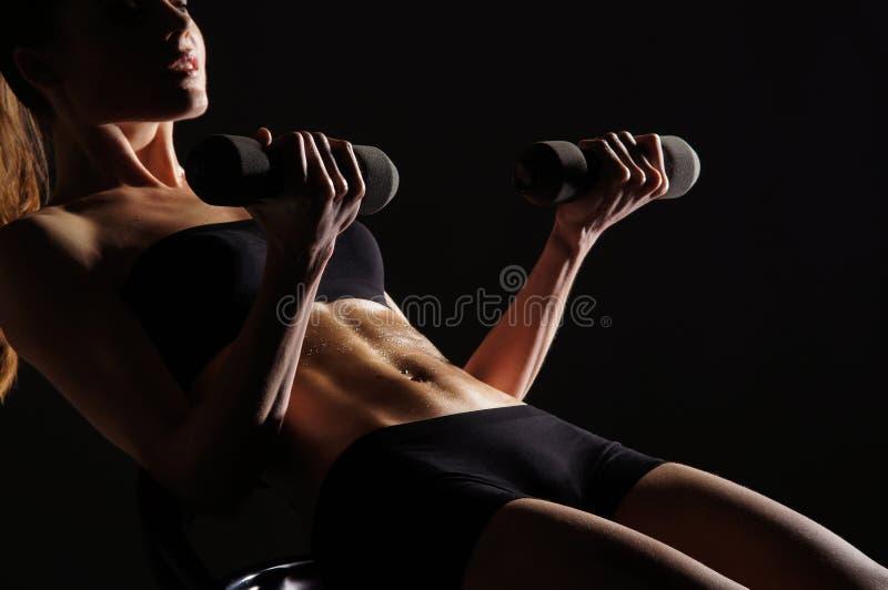 Corpo de uma mulher nova que elabora seu Abs imagens de stock