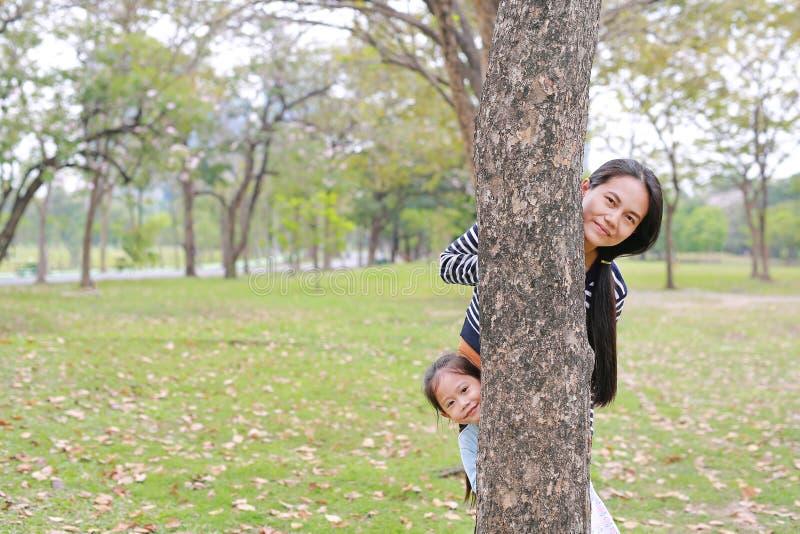 Corpo del pellame della ragazza bambino del piccolo e della mamma asiatica felice dietro il tronco di albero in giardino all'aper immagini stock