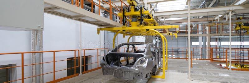Corpo dell'automobile sul primo piano del trasportatore Linea di produzione automobilistica Formato lungo Ampia struttura immagine stock