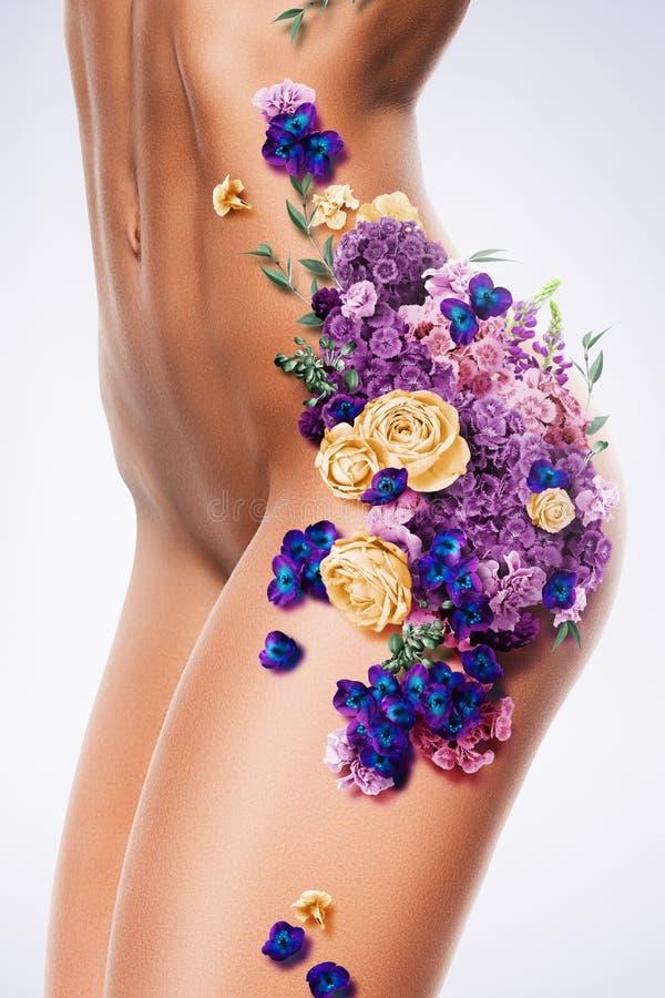 Corpo despido desportivo da mulher nas flores fotografia de stock royalty free