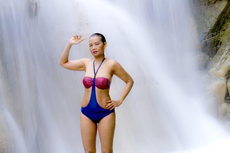 Corpo di manifestazione della donna grande in cascata con il bikini immagine stock libera da diritti
