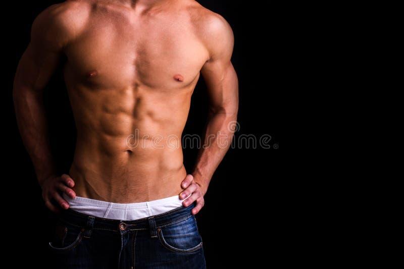 Corpo di un uomo muscolare contro fondo nero fotografia stock