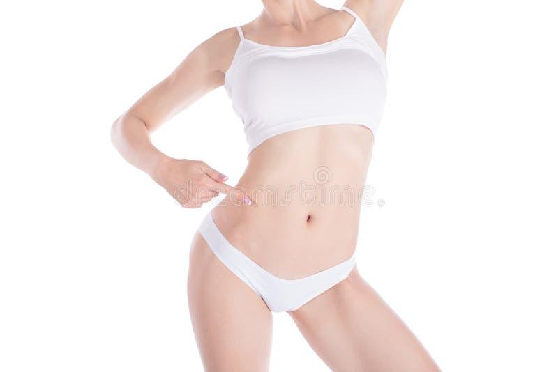 Corpo magro colhido fêmea do ajuste Pontos da mulher a sua cintura delgada com seu dedo Isolado no branco fotos de stock royalty free