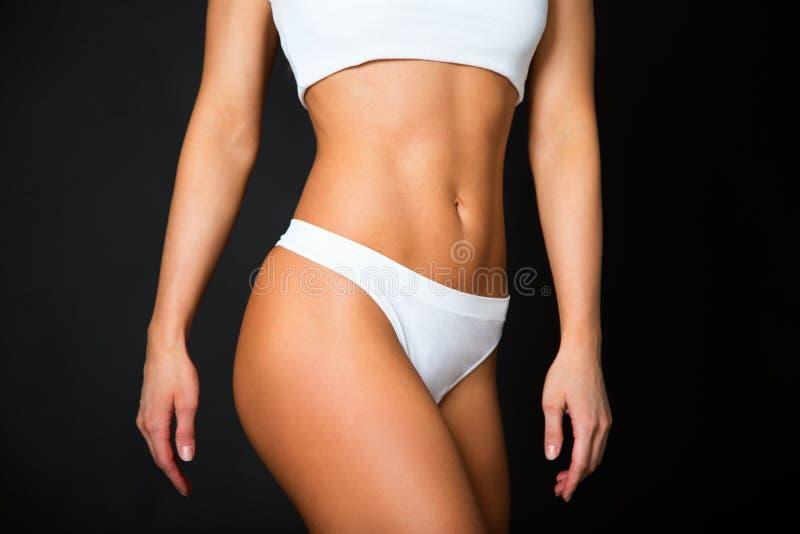 Corpo magro da mulher tanned Isolado sobre o preto imagens de stock royalty free