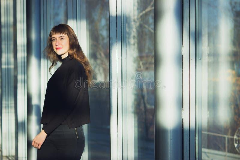 Corpo magro de uma jovem mulher bonita que veste calças de brim pretas imagens de stock