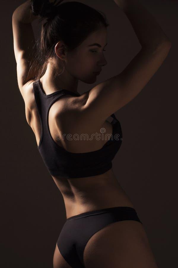 Corpo magro 'sexy' da mulher do ajuste Muscled para trás sportswear Backgro escuro imagens de stock royalty free