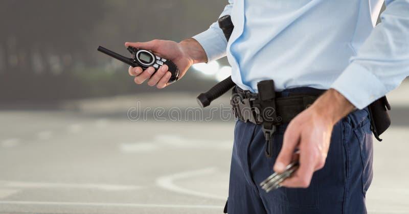 Corpo più basso della guardia giurata con il walkie-talkie contro la via confusa fotografie stock