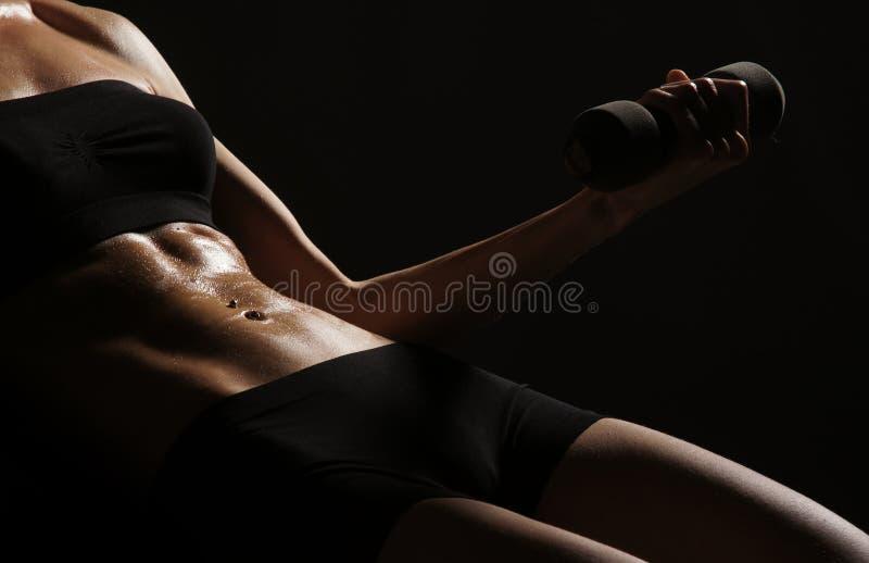 Corpo 'sexy' de uma mulher nova que elabora seu Abs fotografia de stock royalty free