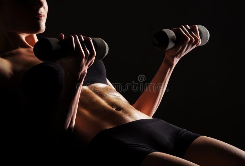 Corpo 'sexy' de uma mulher nova que faz o exercício do Abs fotografia de stock