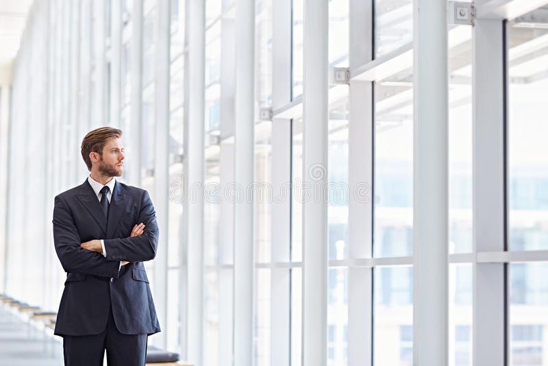 Corporate ambitions. Corporate executive in a modern architectural setting looking confidently out of high rise windows stock photo