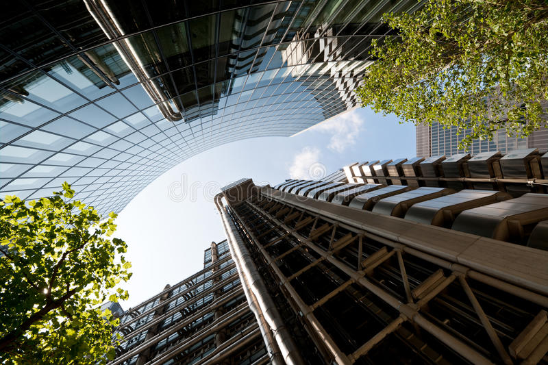 Corporate Building London, UK. Looking up the the futuristic metal facade of Lloyd's London, reflecting in glass corporate building stock photography