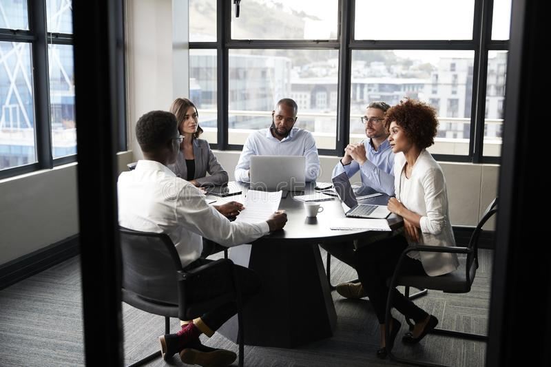 Corporate business colleagues talking in a meeting room, seen from doorway stock photo