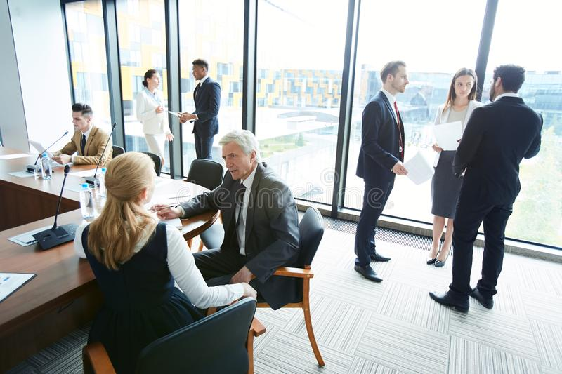 Corporate business. Large group of business people in formalwear discussing work issues in spacious conference room and being in different place of room royalty free stock photos