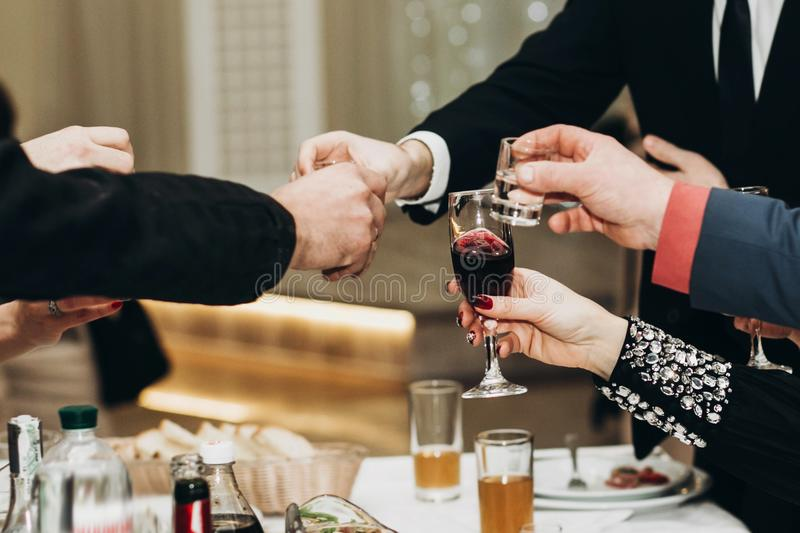 Corporate business man toasting at dinner party table hands close-up, wedding reception guests toast alcohol drinks in glasses stock photo