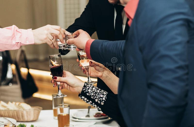Corporate business man toasting at dinner party table hands close-up, wedding reception guests toast alcohol drinks in glasses stock photography