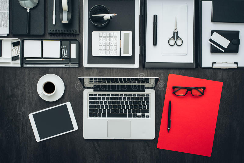 Corporate business office. Desktop with laptop, tablet and office accessories, flat lay royalty free stock image
