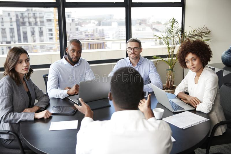 Corporate business people in a meeting room listening to a colleague speaking, elevated view royalty free stock photography