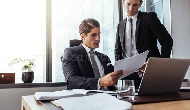 Corporate business people reading papers in office royalty free stock photography