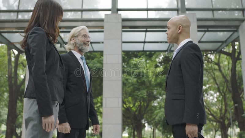 Corporate business people talking in building lobby stock photos