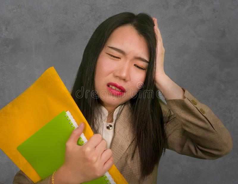 Corporate business stress portrait of young attractive upset and stressed executive Asian Chinese woman tired and unhappy holding. Paperwork overwhelmed and stock photos