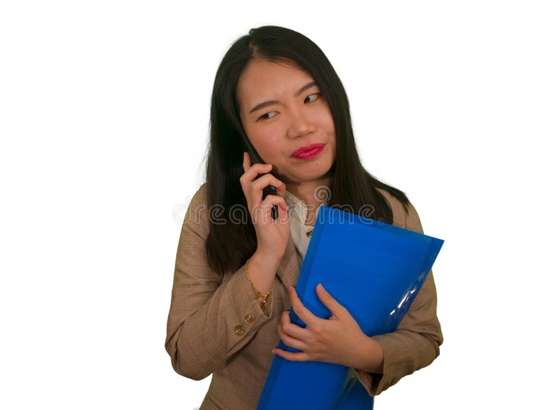 Corporate business stress portrait of young attractive upset and stressed executive Asian Korean woman talking on mobile phone. Tired and unhappy holding royalty free stock photo