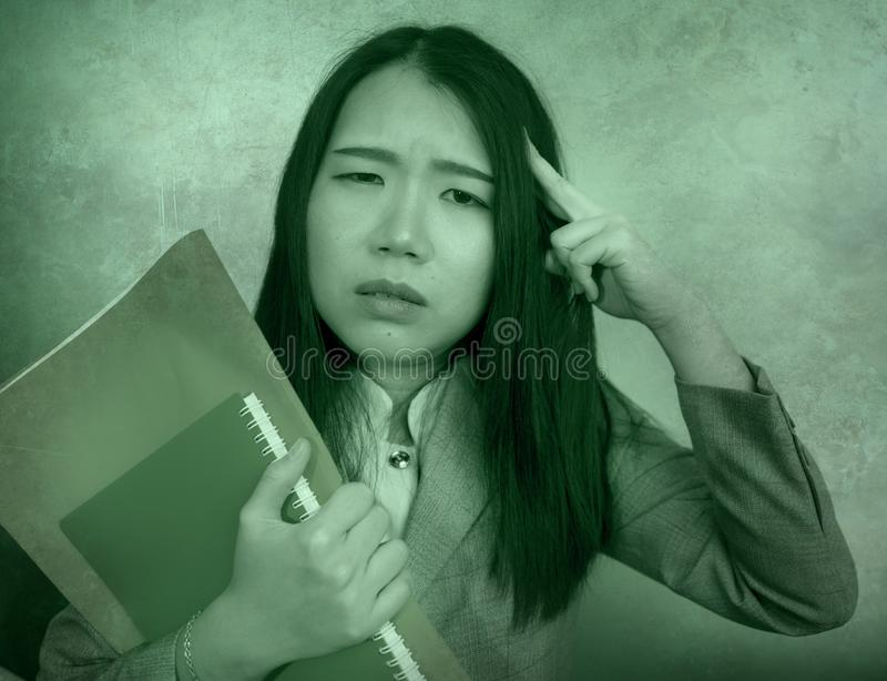Corporate business stress portrait of young attractive upset and stressed executive Asian Korean woman tired and unhappy holding. Paperwork overwhelmed and stock image