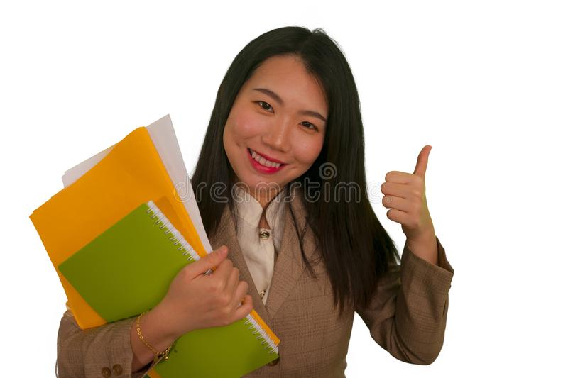 Corporate business success portrait of young attractive happy and confident executive Asian Chinese woman holding paperwork folder. Smiling cheerful giving stock photography
