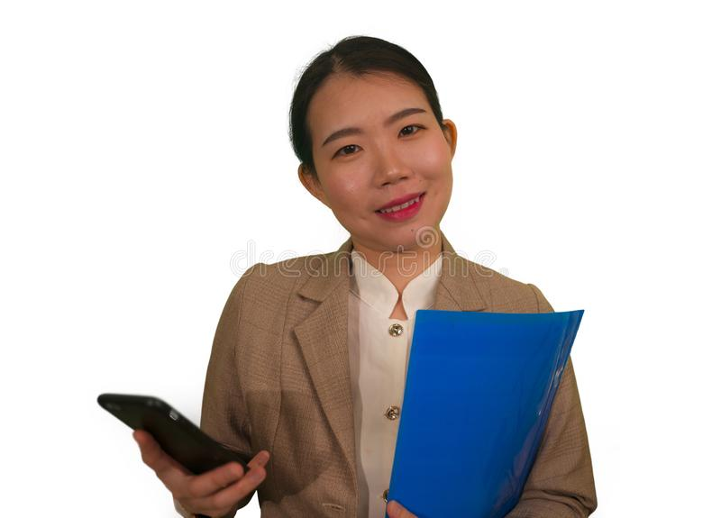 Corporate business success portrait of young attractive happy and confident executive Asian Korean woman holding mobile phone and. Folder smiling cheerful in stock image