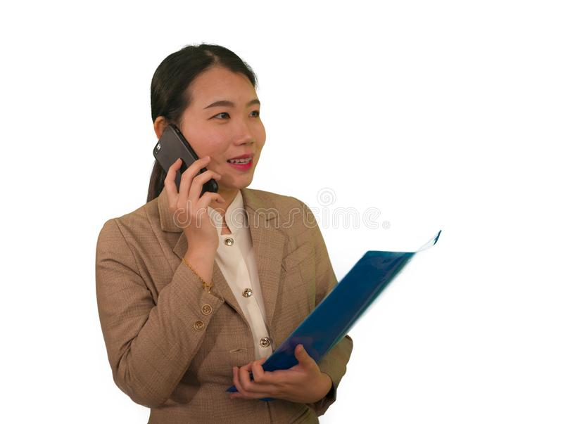 Corporate business success portrait of young attractive happy and confident executive Asian Korean woman talking on mobile phone. Holding folder smiling stock photo