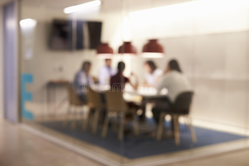 Corporate business team at table in a meeting room cubicle, defocussed royalty free stock image