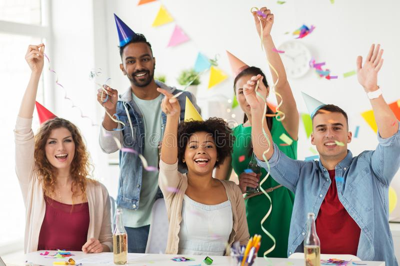 Happy team with confetti at office birthday party. Corporate, celebration and holidays concept - happy team with confetti and serpentine having fun at office royalty free stock images