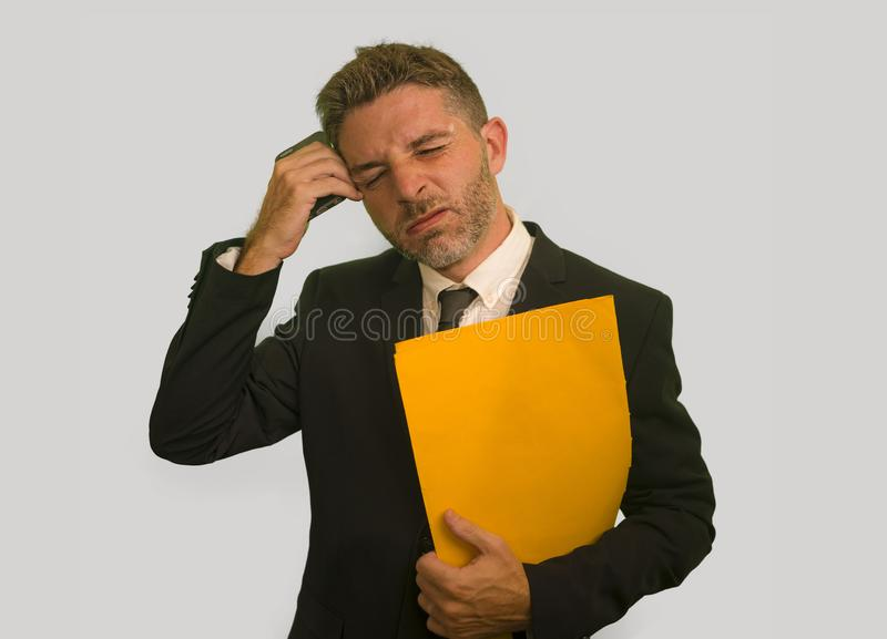 Corporate company work lifestyle portrait of stressed and frustrated businessman holding paperwork reports overwhelmed and upset royalty free stock photo