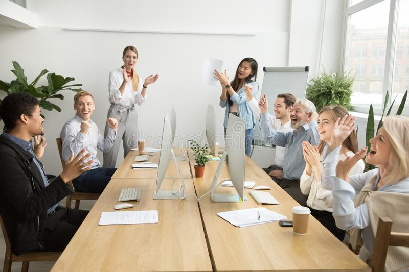 Corporate diverse team congratulating african coworker with busi. Corporate diverse team colleagues congratulating motivated african coworker with business royalty free stock image