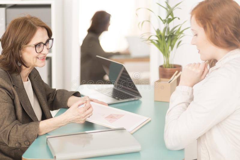 Professional life advisor and employee. Corporate employee consulting personal goals with smiling professional life advisor stock image