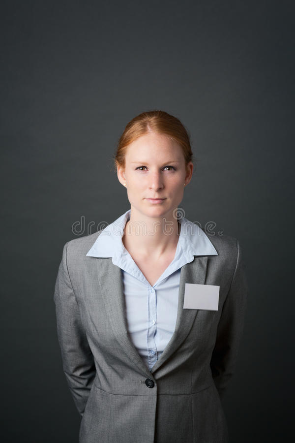 Corporate Employee with Name Tag. A determined young corporate employee wearing a gray suit with a blank name tag poses before a dark background royalty free stock photos