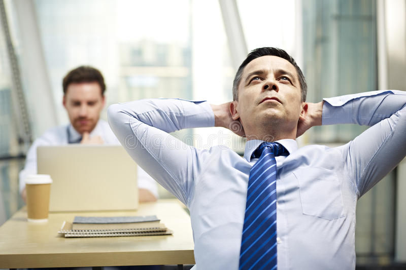 Corporate executive thinking in office stock photography