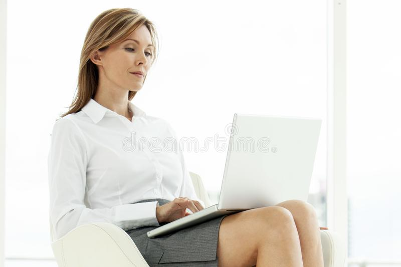 Corporate executive woman using laptop in contemporary location royalty free stock photos