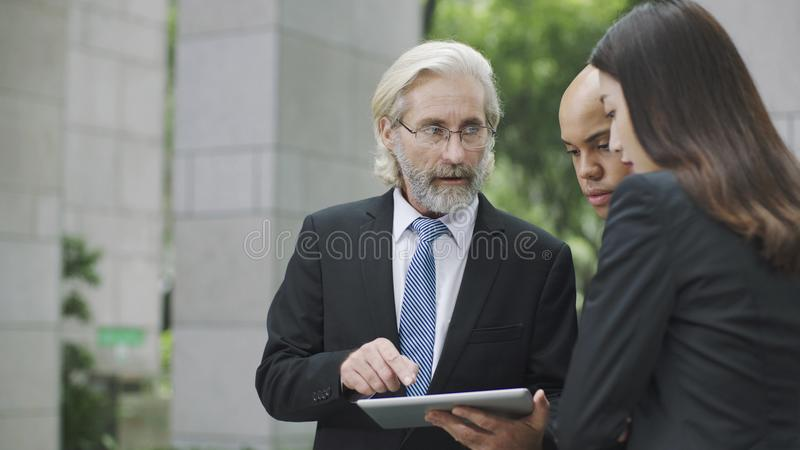 Corporate executives discussing business using digital tablet stock images