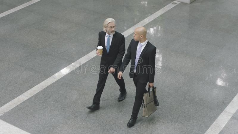 Corporate executives walking across lobby of office building royalty free stock image