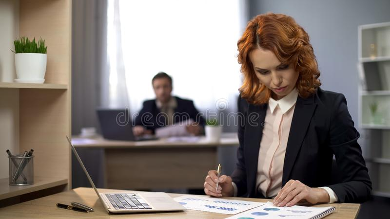 Corporate female employee sitting at desk, checking charts, thinking of results stock photos