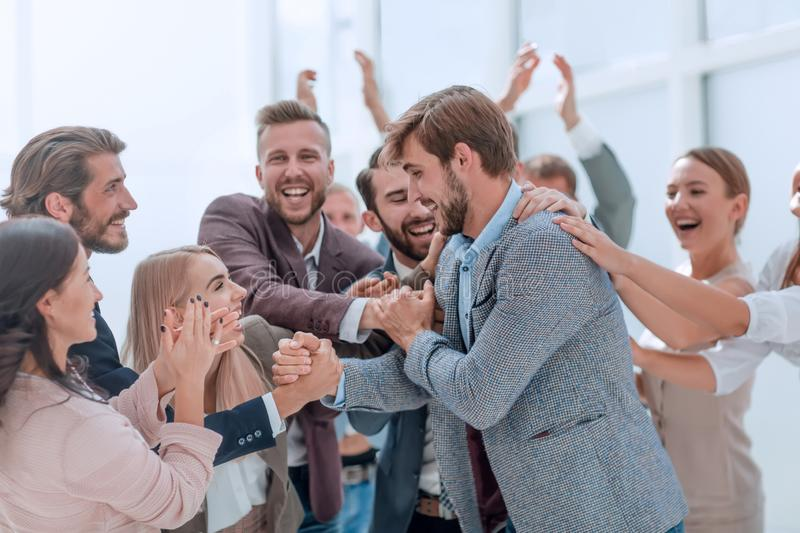 Corporate group of employees applauding their colleague. stock images