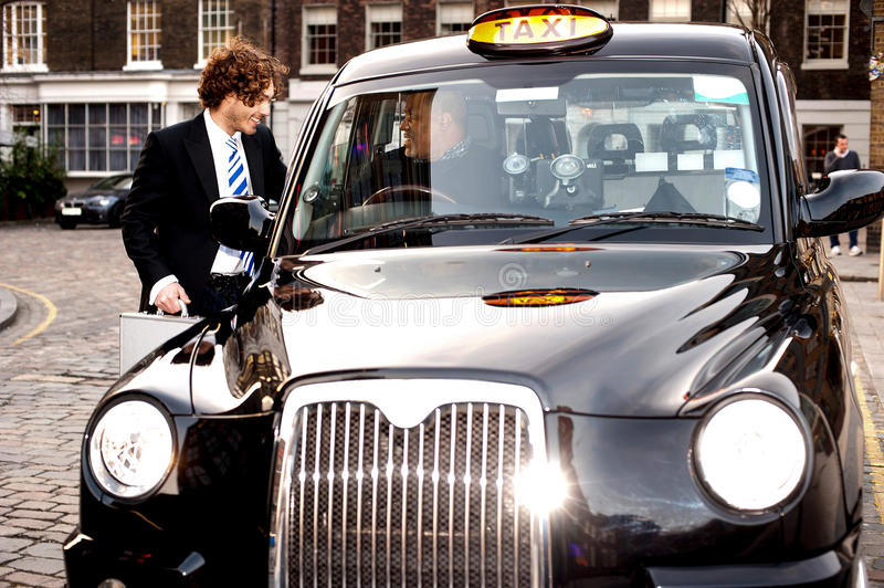 Corporate guy interacting with taxi driver. Taxi cab driver communicating with male passenger stock image