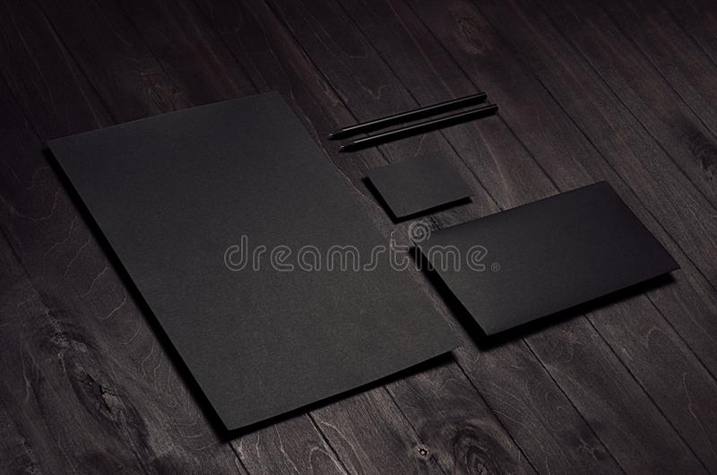 Corporate identity set of blank black letterhead, envelope, business card on dark wood board, inclined. stock images