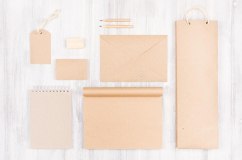 Corporate identity template; packaging, stationery, gift mock up of brown kraft paper on soft white wood background. royalty free stock photo
