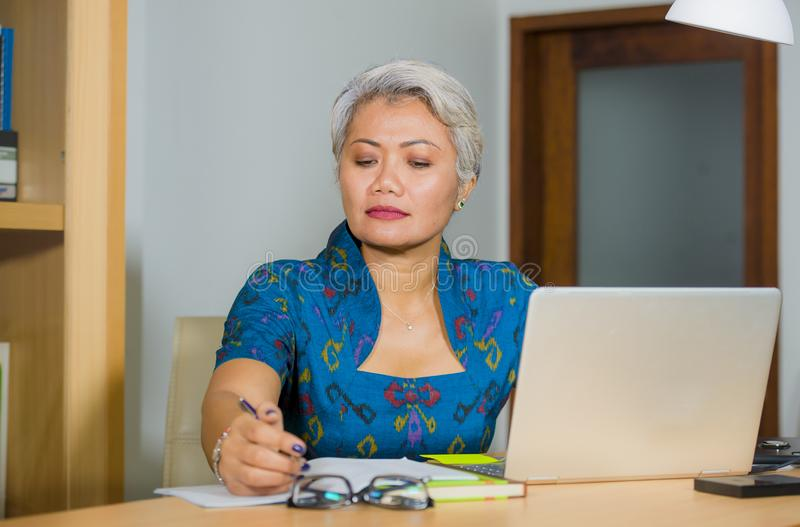 Busy and concentrated attractive middle aged Asian woman working at office laptop computer desk focused and efficient in business stock photo