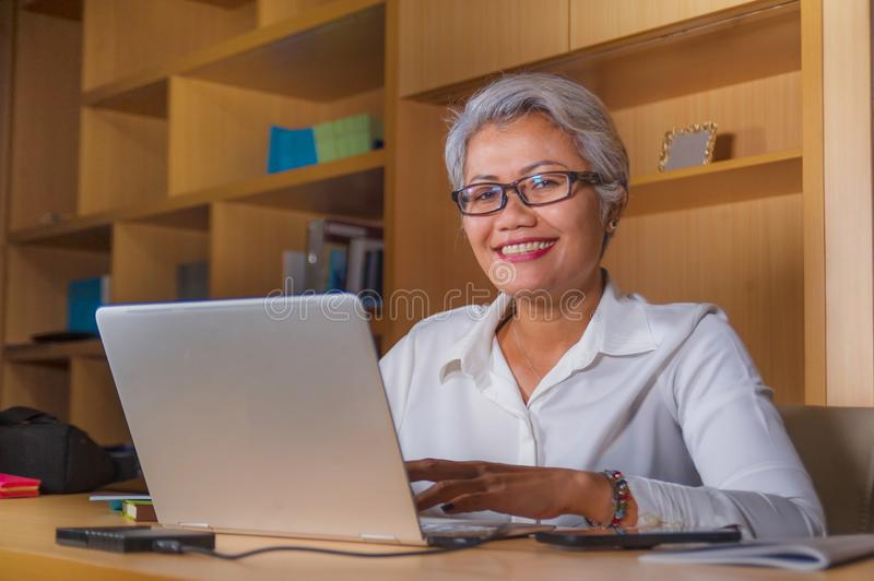 Corporate job lifestyle portrait of happy and successful attractive middle aged Asian woman working at office laptop computer desk stock image