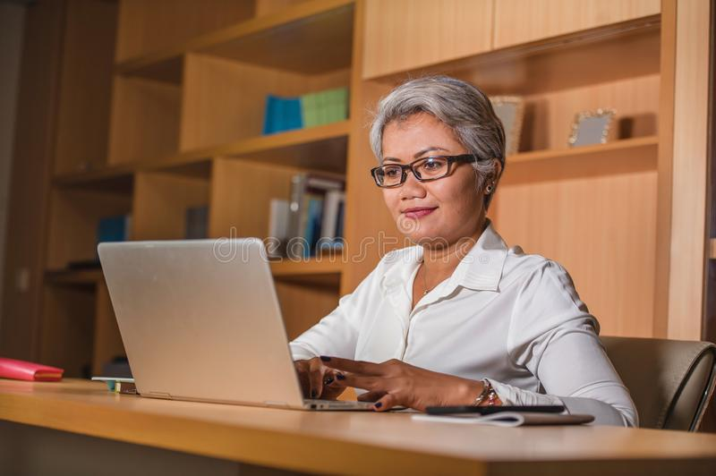 Corporate job lifestyle portrait of happy and successful attractive middle aged Asian woman working at office laptop computer desk royalty free stock image