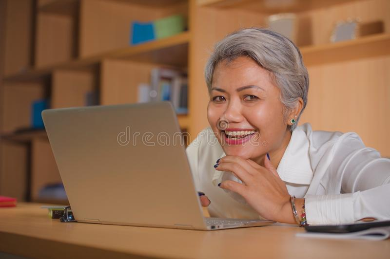 Corporate job lifestyle portrait of happy and successful attractive middle aged Asian woman working at office laptop computer desk stock images