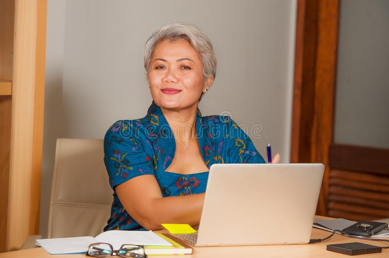 Corporate job lifestyle portrait of happy and successful attractive middle aged Asian woman working at office laptop computer desk royalty free stock photo