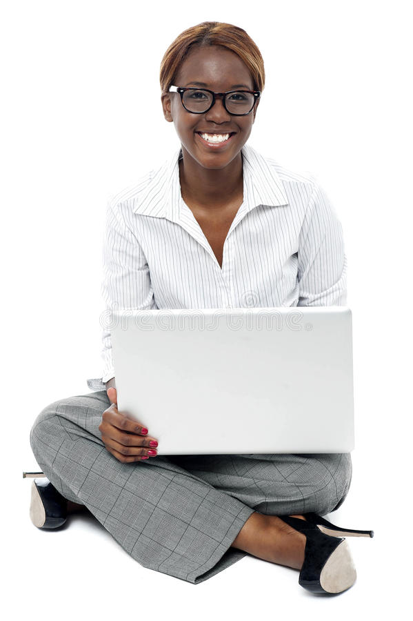 Corporate lady seated on floor working on laptop stock images
